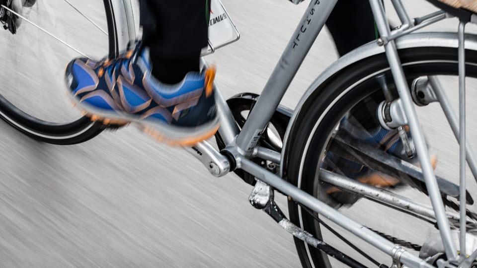 Närbild på skor som trampar en cykel.