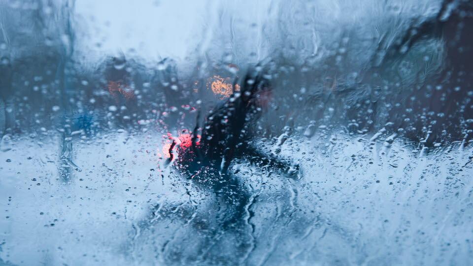 Cyklist genom ett regnstrimmat fönsterglas.