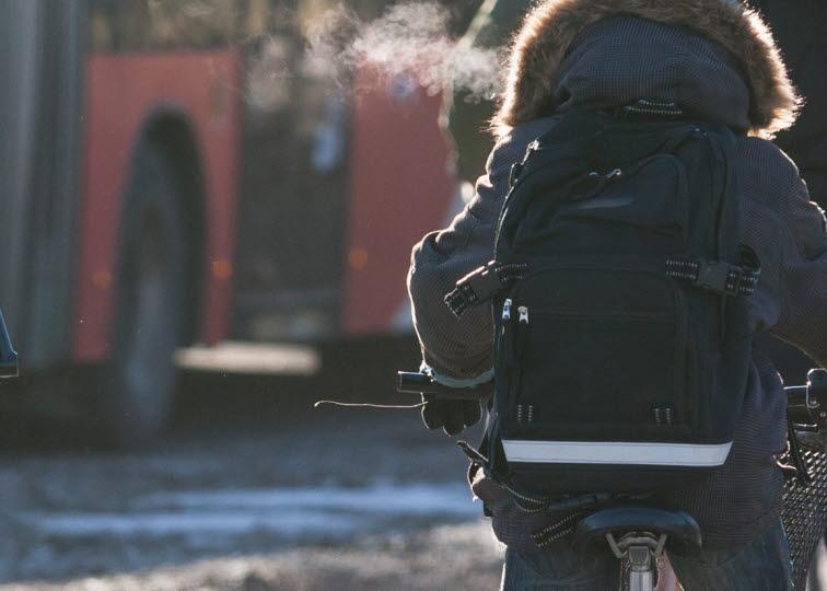 Ungdom på cykel mad buss i bakgrund.