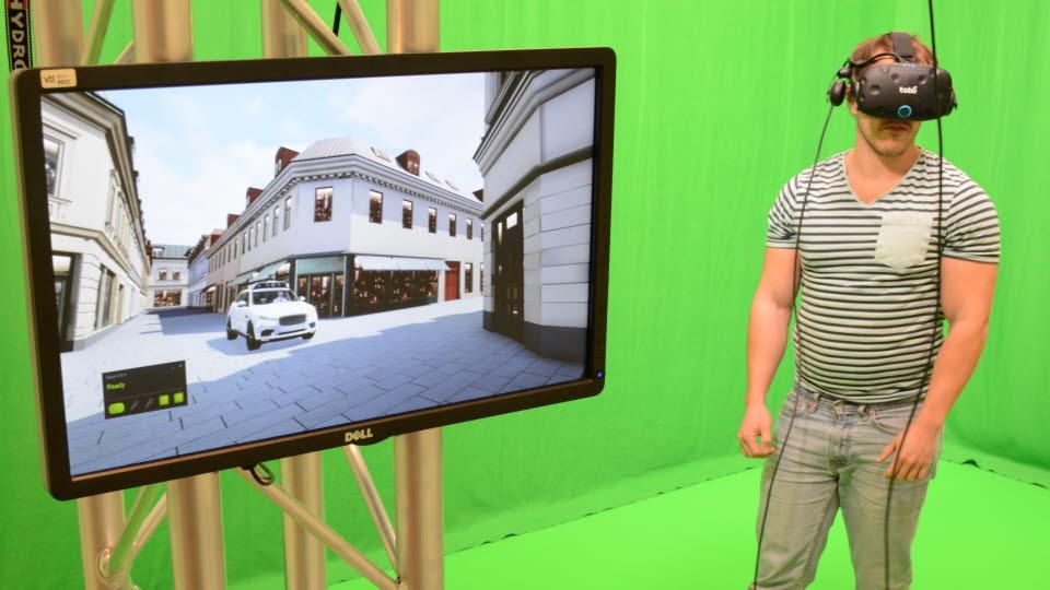 Kille med VR-hjälm och en bildskärm som visar simulering.