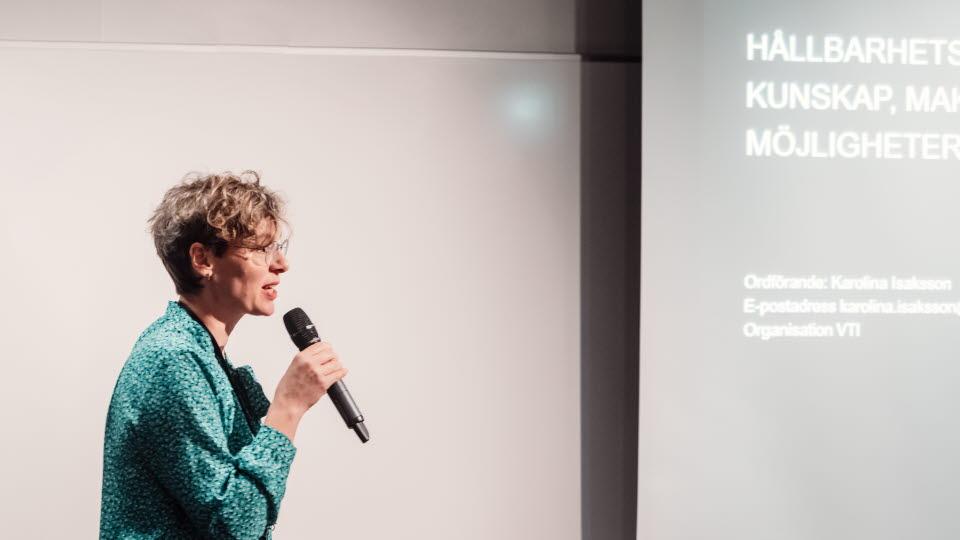 Kvinna håller en mic och föreläser.