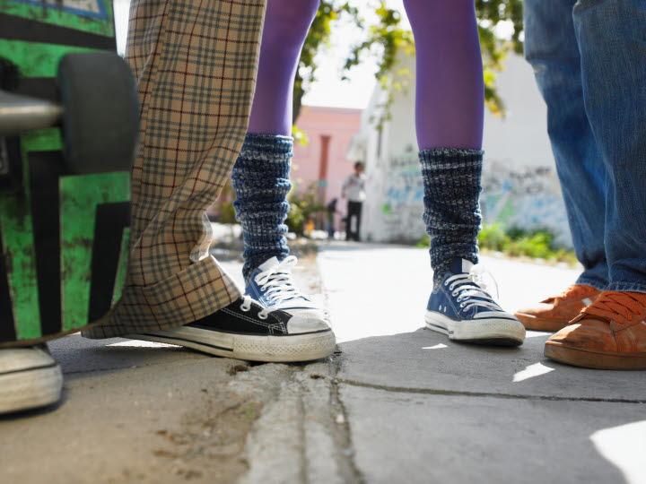 Ungdomars ben och skor syns utanför skolbyggnad.