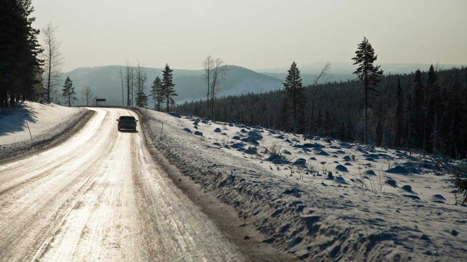 Bil kör på en vinterväg.