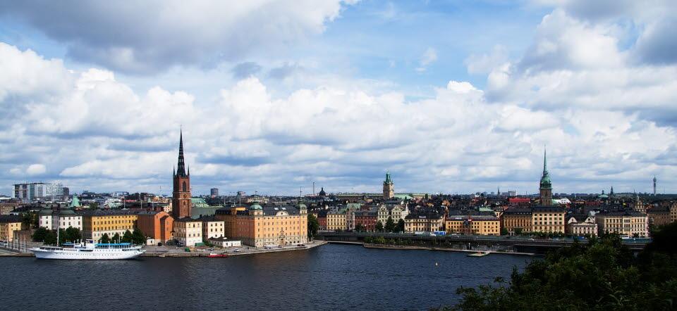Vy över Stockholm. Vatten i förgrunden, kaj och byggnader.