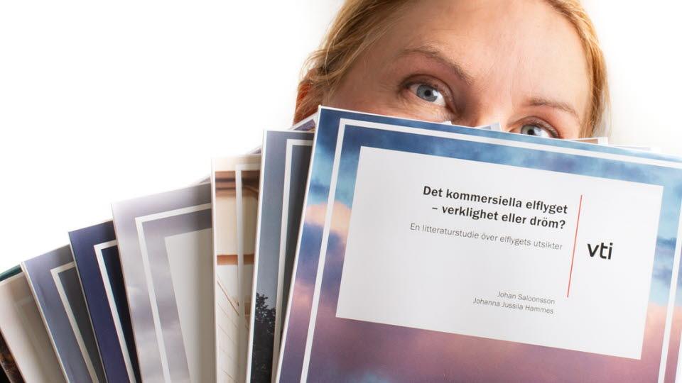 Kvinna som visar upp publikationer.